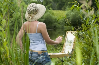 Woman painting by lake